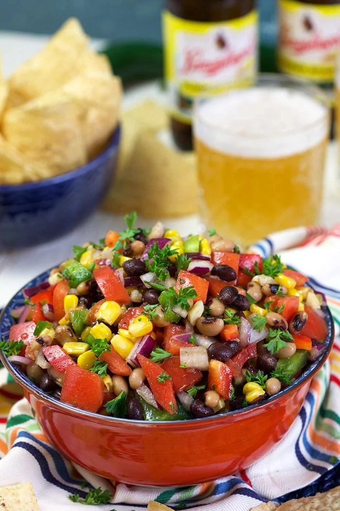Cowboy Caviar in a red bowl with a beer in the background.
