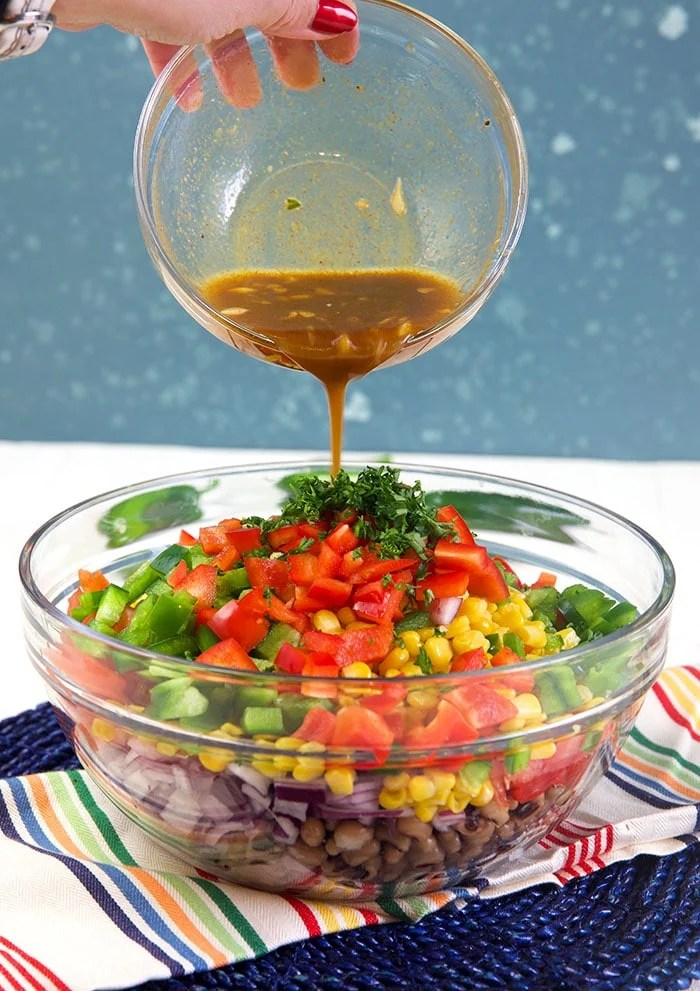 Dressing being poured over Texas caviar ingredients in a bowl.