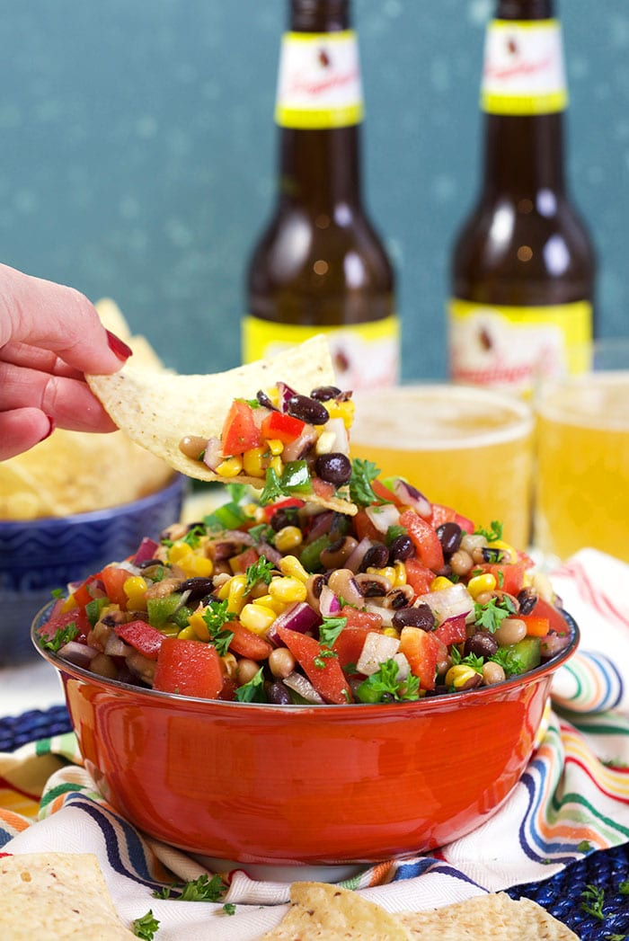 Cowboy Caviar in a red bowl with a chip dipping into it.