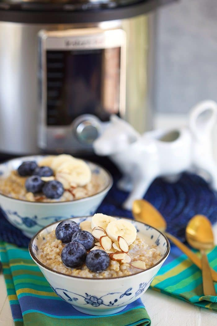 Oatmeal in a blue and white bowl with blueberries and an instant pot in the background.