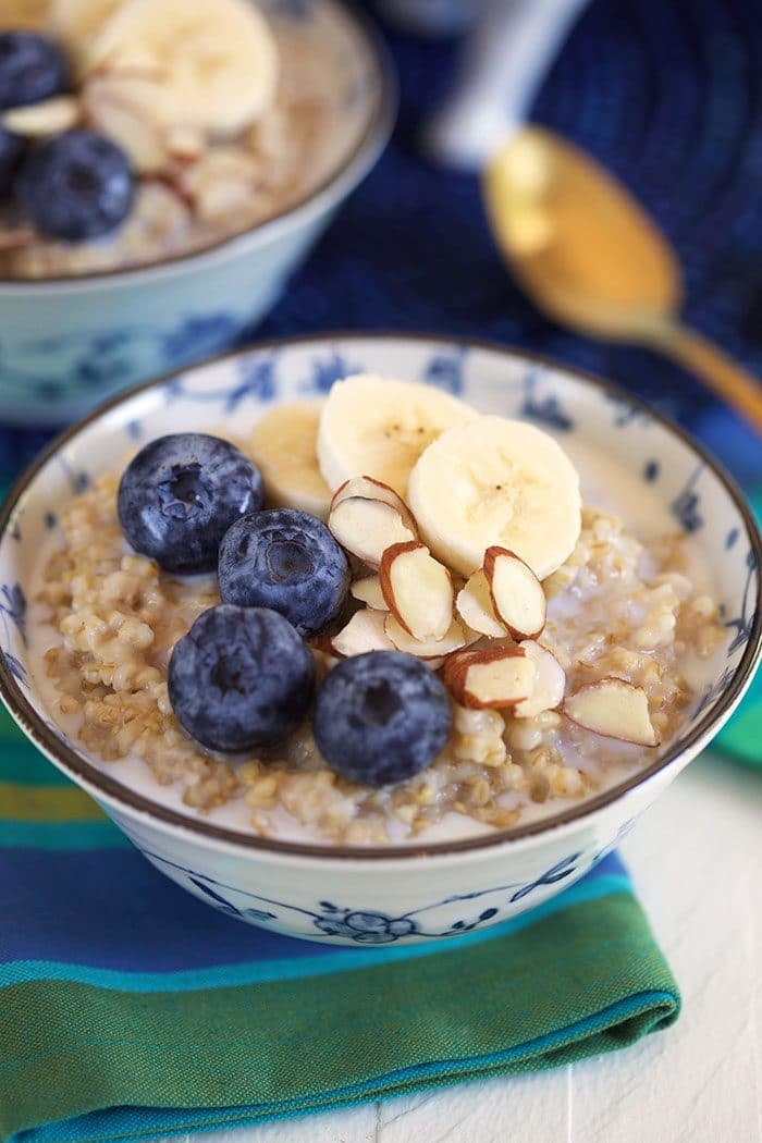 Steel cut oatmeal in a blue and white bowl with blueberries, bananas and almonds.