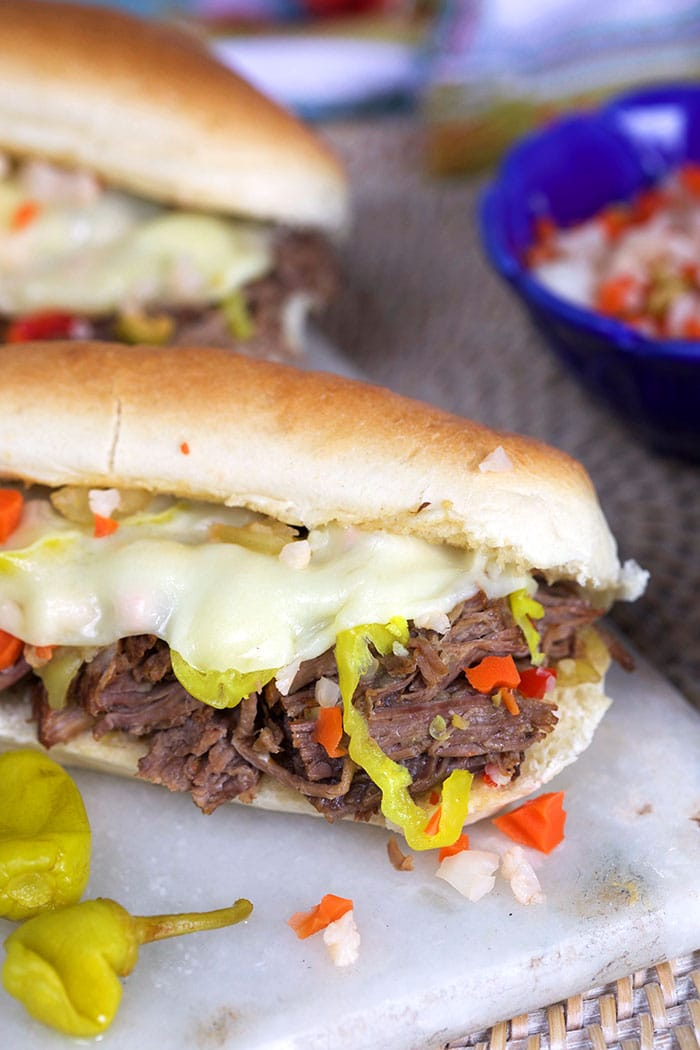 Close up of shredded italian beef on a long roll.