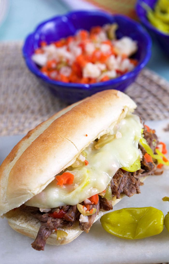 Italian Beef Sandwich on a long roll with a blue bowl of giardiniera in the background.