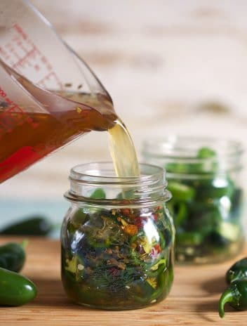 pickle brine poured into a jar with jalapeno peppers.
