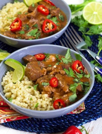 Thai Red Curry Beef Stew on a bed of couscous in a blue bowl.
