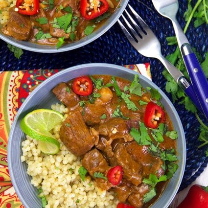 Overhead shot of thai red curry beef on a bed of couscous with a lime.