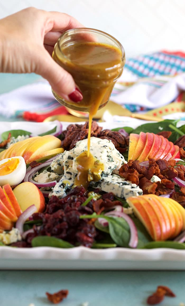 Hot Bacon Dressing being poured on a spinach salad.