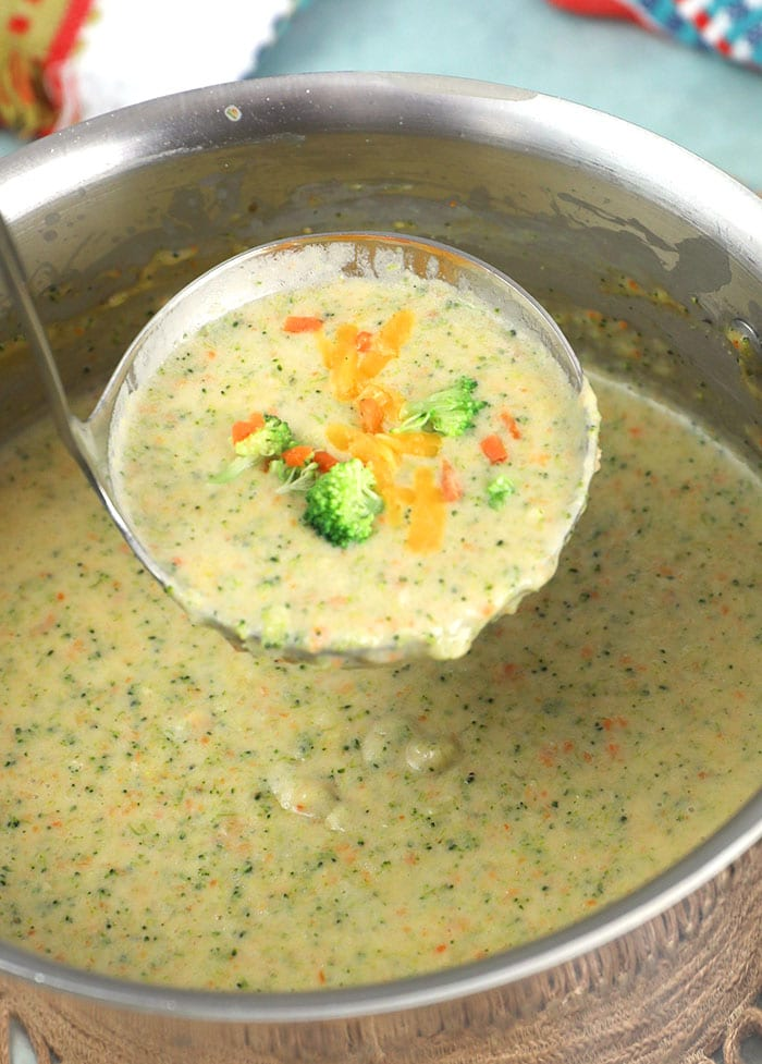 Big pot of broccoli cheddar soup with a ladle scooping a serving.