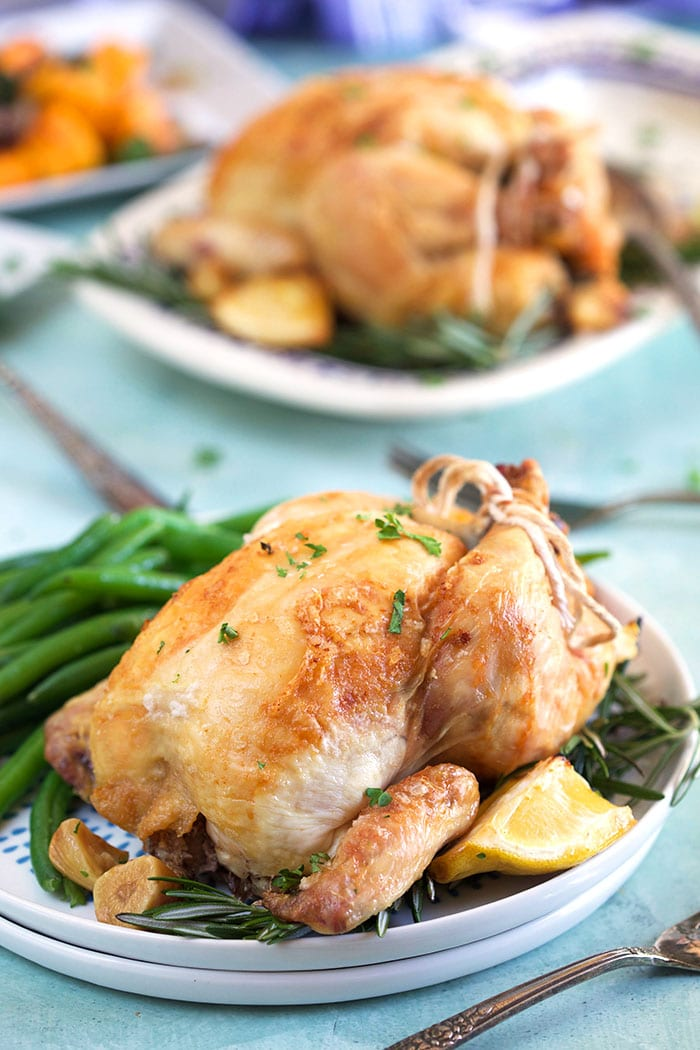 Cornish hen on a white plate with roasted lemon and green beans.