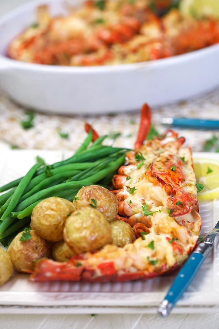 Lobster thermidor on a plate with potatoes and green beans.