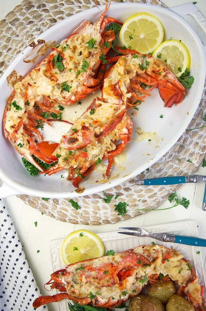 Overhead lobster thermidor in a baking dish with lemons.