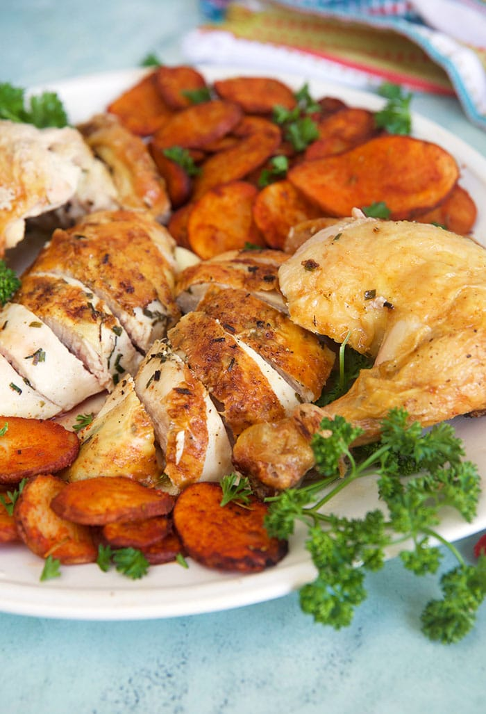 Oven roasted chicken on a white platter with potatoes.