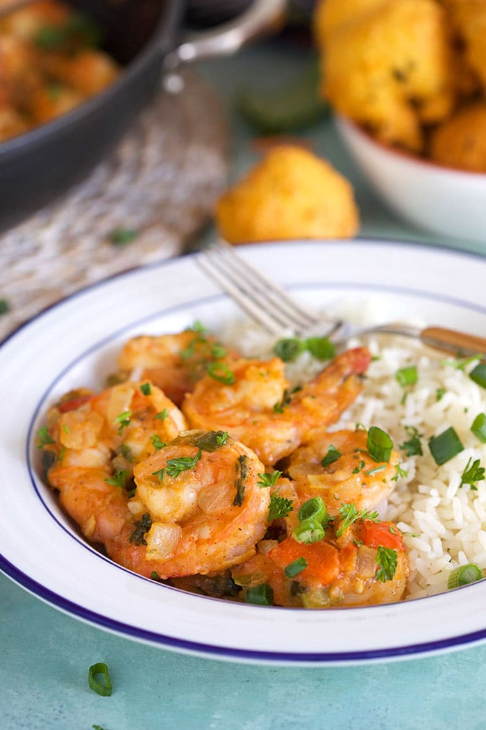Close up of shrimp etouffee in a white bowl with rice.