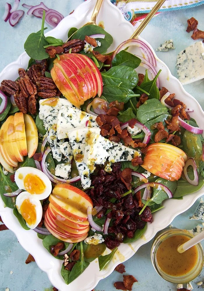 A large square white platter is totally filled with autumn apple salad.