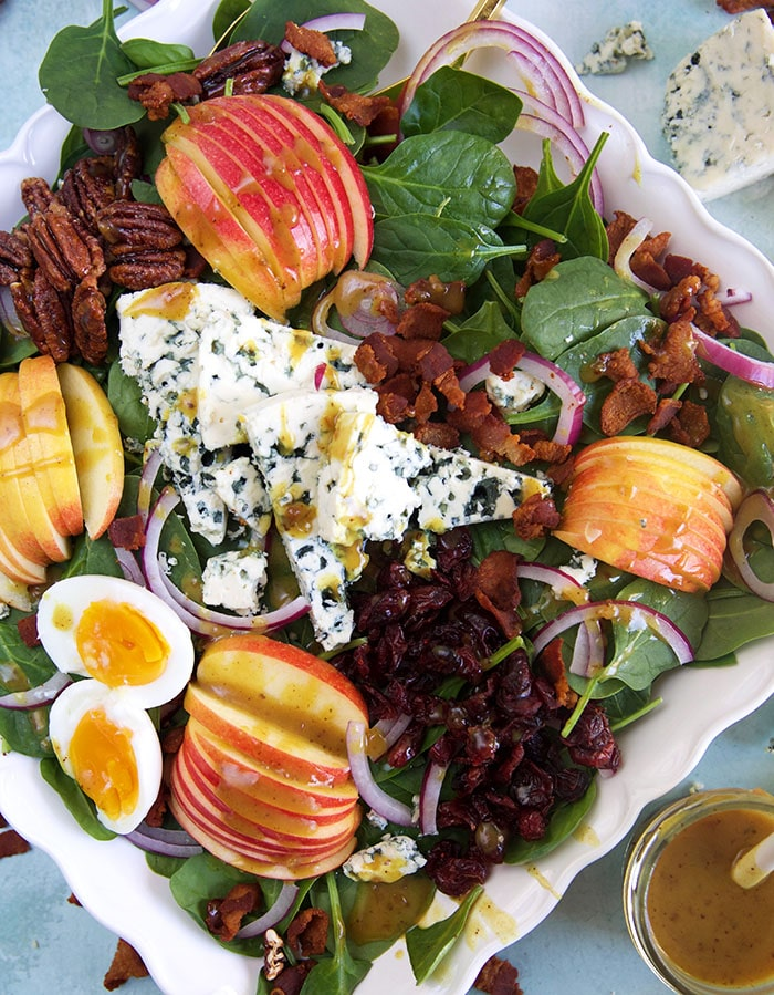 A spinach salad is loaded with ingredients like nuts, hard boiled eggs and apple slices.