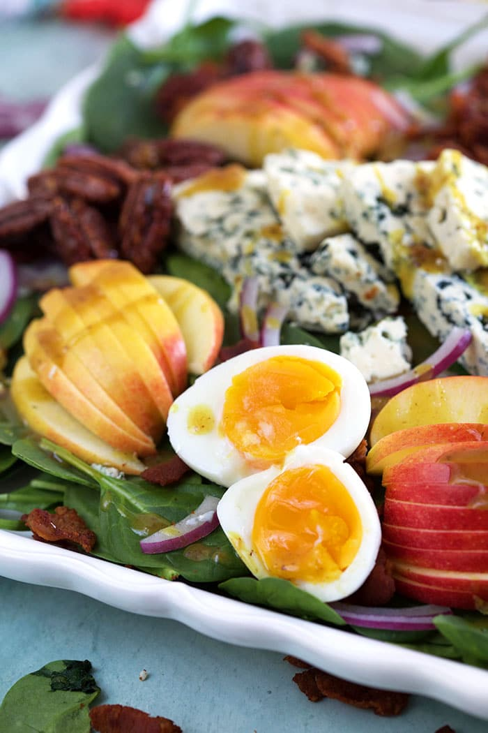 Hard boiled eggs, cheese, apples and spinach are all in one large white serving tray.