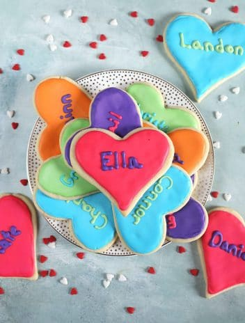 Overhead shot of valentine sugar cookies on a white plate.