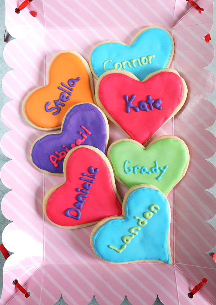 Overhead shot of Valentine cookies on a pink tray.