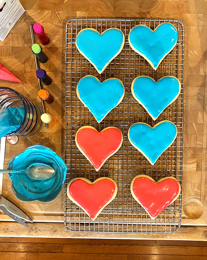 Overhead shot of heart cookies being decorated with royal frosting.