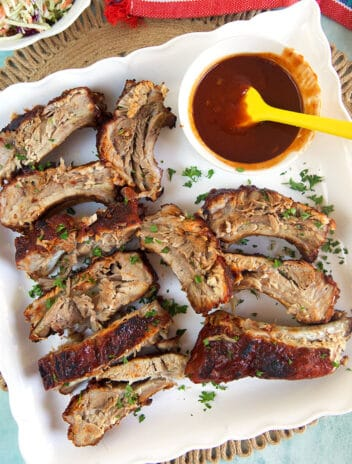 BBQ Pork ribs on a white platter with a bowl of sauce.