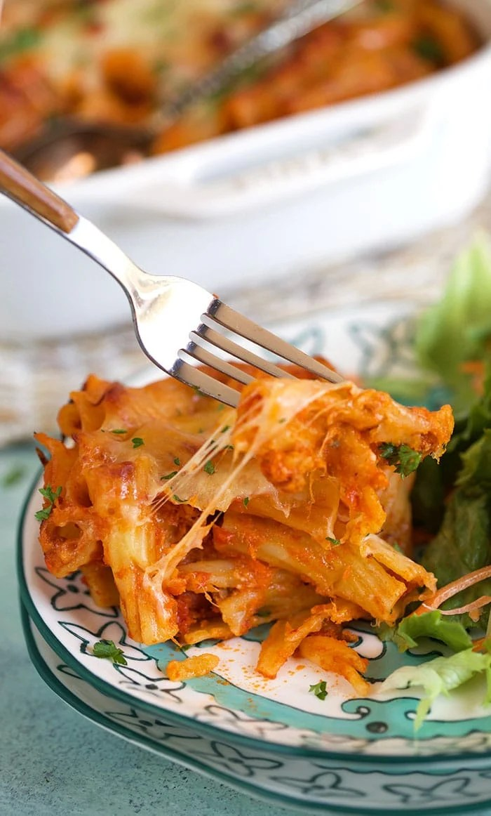 Baked Rigatoni on a plate with a fork taking a bite.