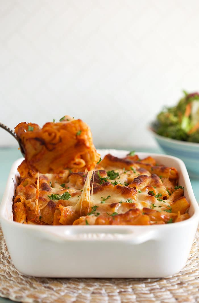 Baked Rigatoni Bolognese being served with a cheese pull into the dish.