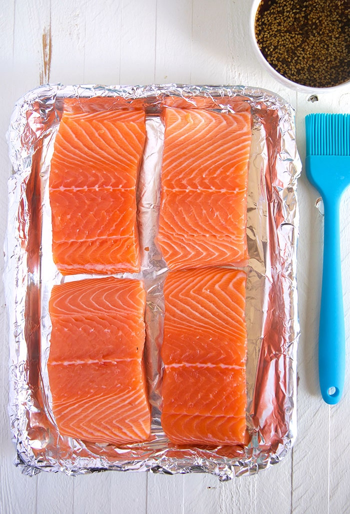 Overhead shot of salmon filets on a baking sheet lined with foil.