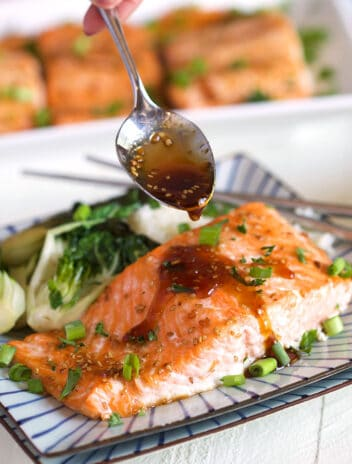 Baked Teriyaki Salmon with teriyaki sauce being drizzled on top with a spoon.