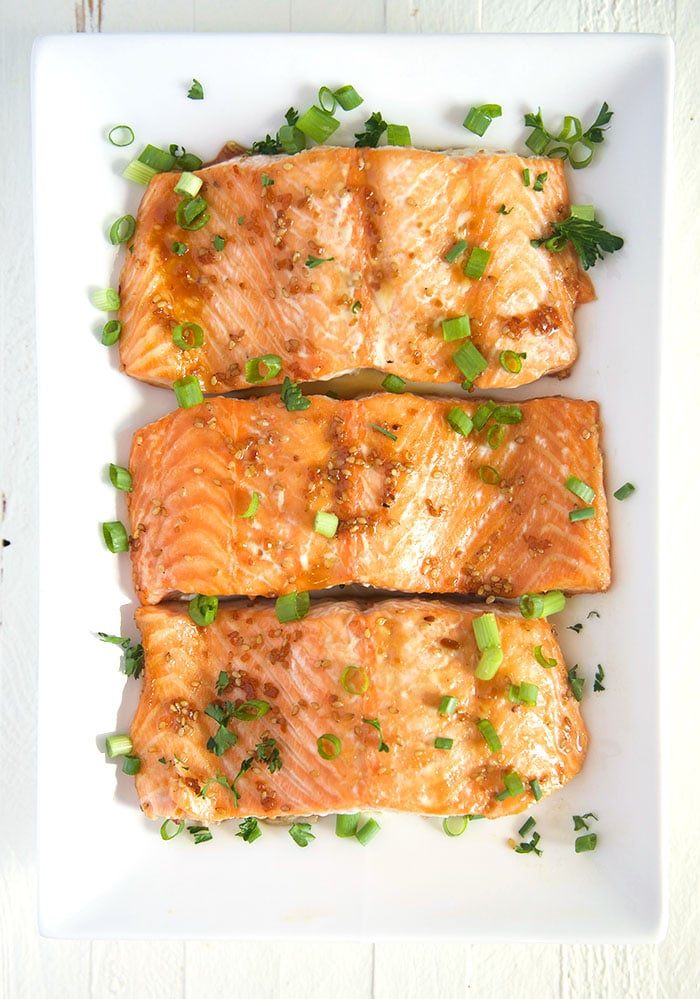 Overhead shot of baked teriyaki salmon on a white rectangle platter.