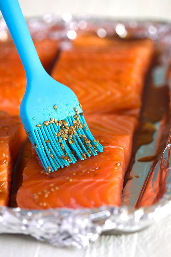 Blue basting brush applying teriyaki sauce to salmon filets on a baking sheet.