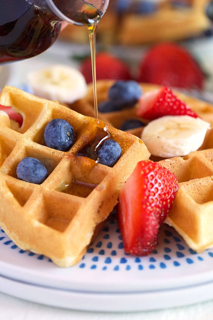 Belgian waffle on a white plate with fruit.