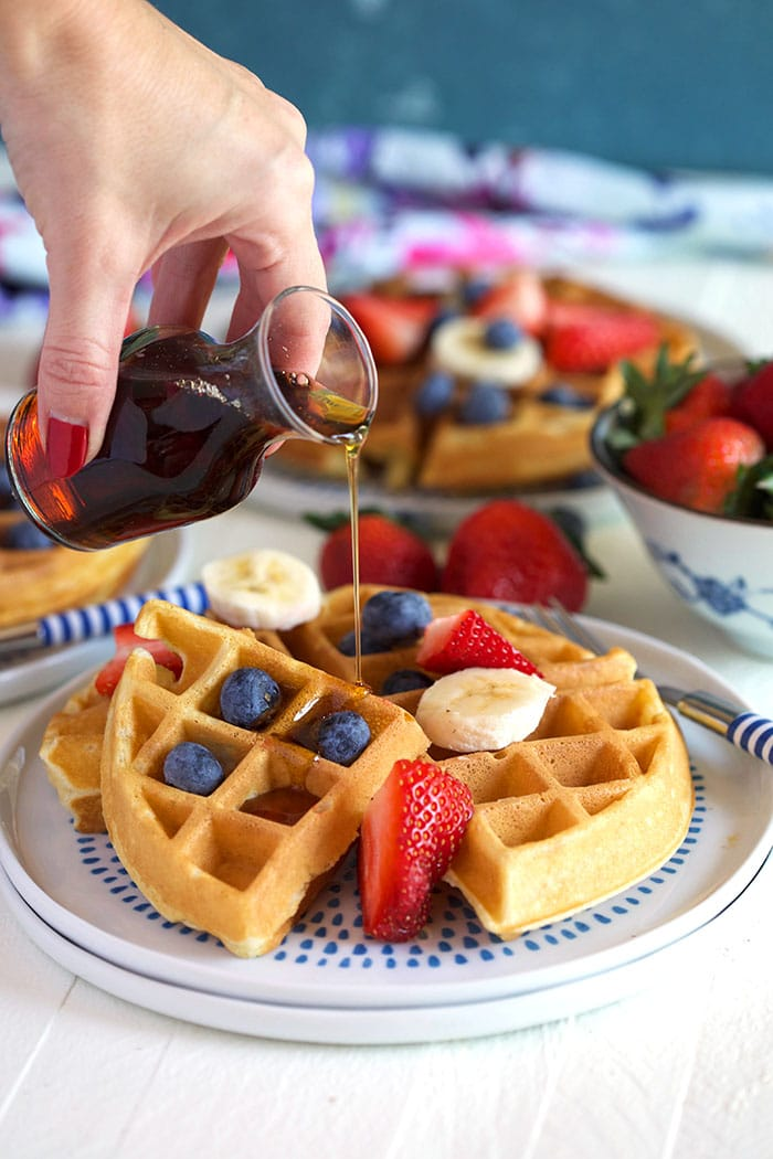 Belgian Waffle with fruit and syrup being poured over top.