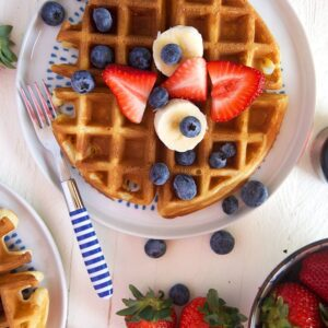 Belgian Waffle with fruit on a white plate.