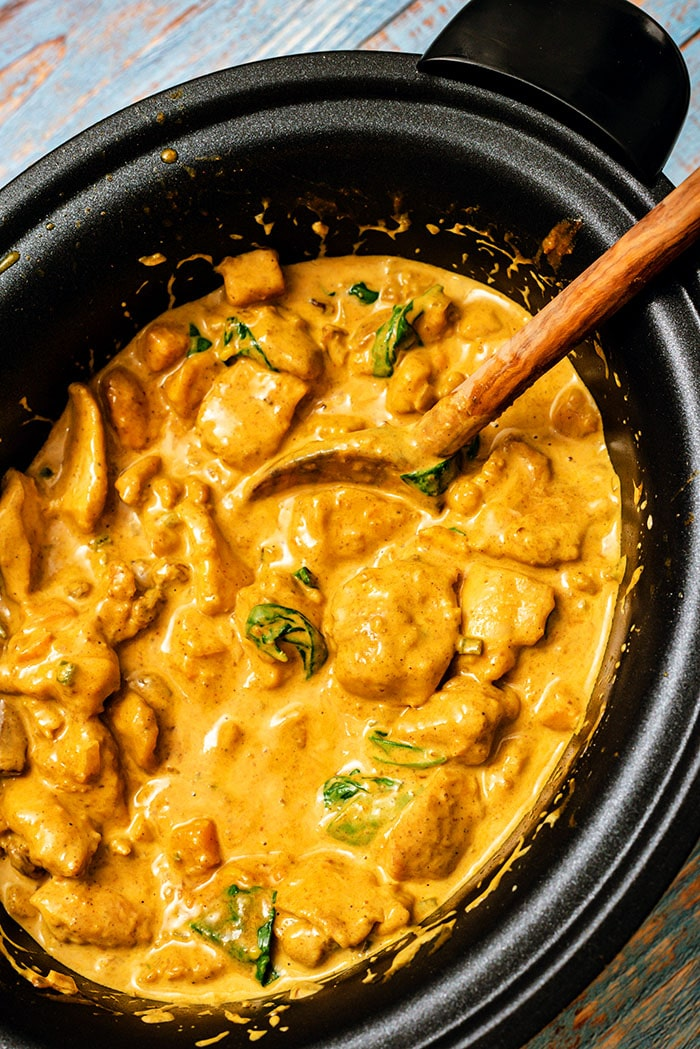 Overhead shot of butter chicken in a slow cooker with a wooden spoon.