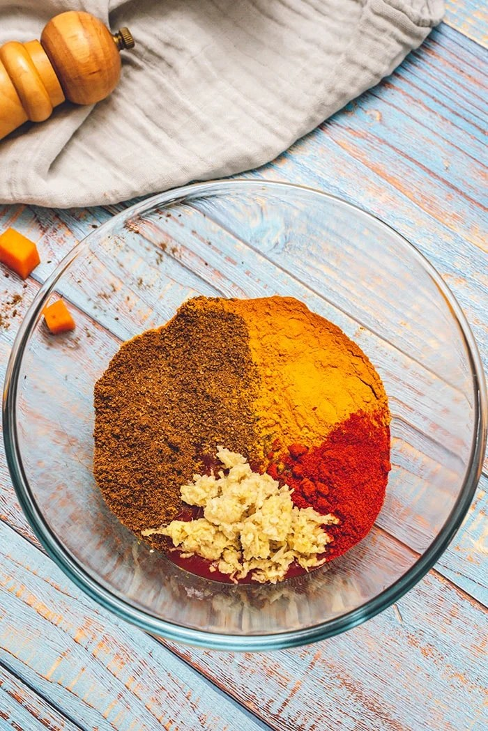 Spices for butter chicken in a glass bowl.