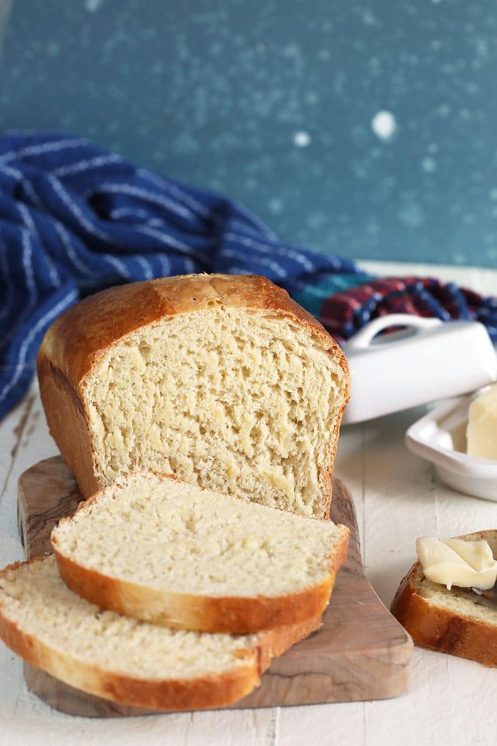 Homemade white bread sliced on a bread board.