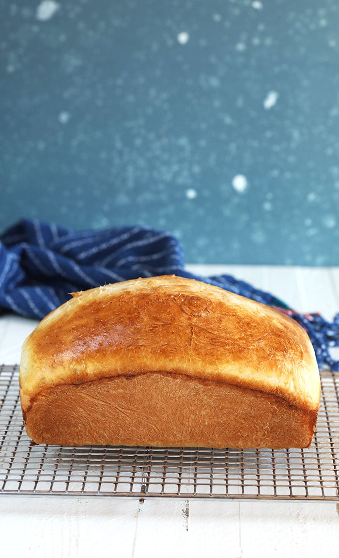Homemade white bread on a cooling rack.