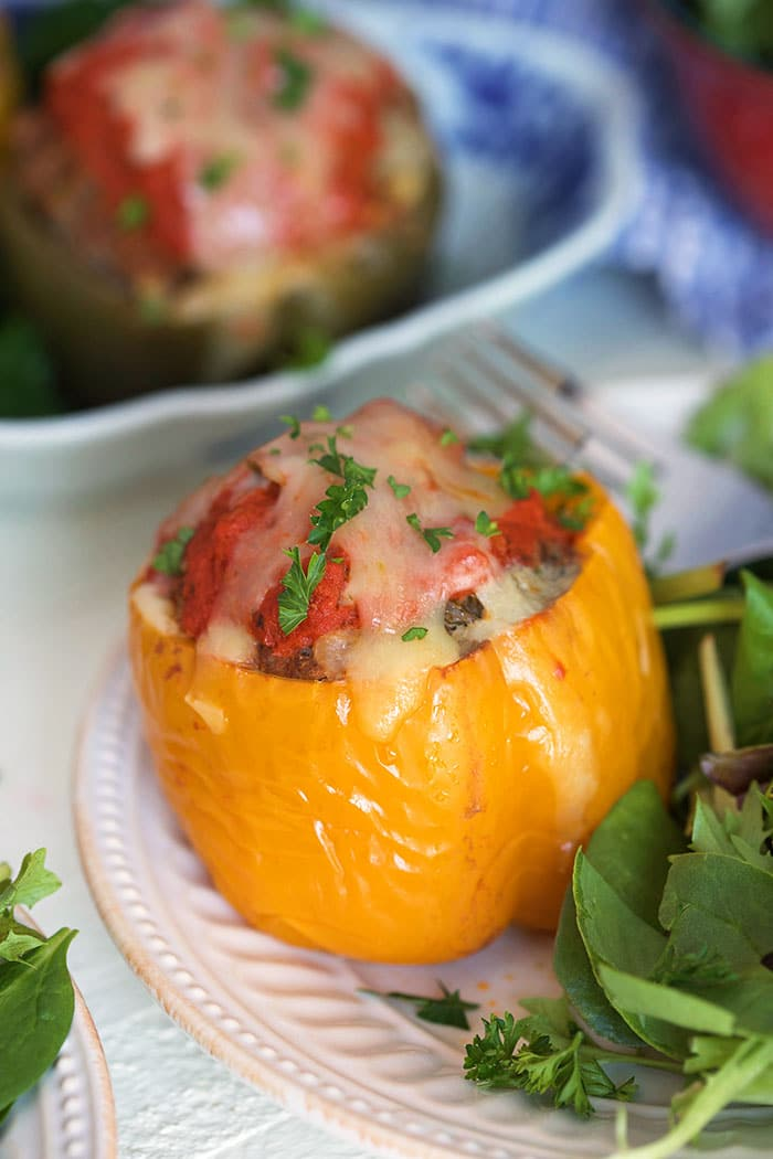 Stuffed yellow bell pepper on a white plate.