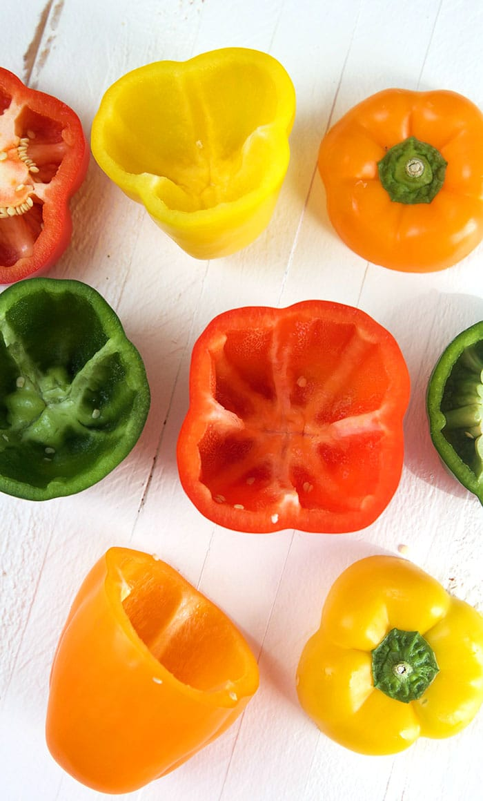 Bell peppers prepped to be stuffed on a white background.