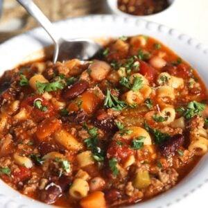Pasta e fagioli in a white bowl with a silver spoon.