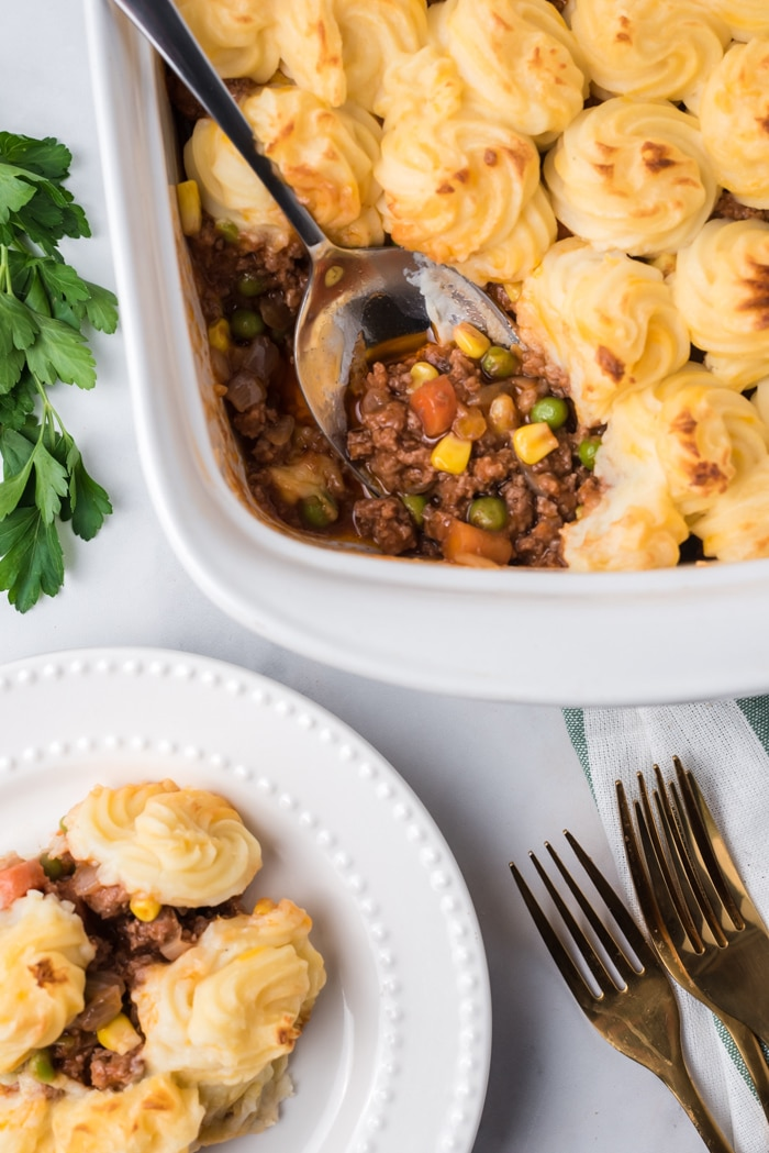 Overhead shot of shepherd's pie in a white casserole dish with a serving spoon.