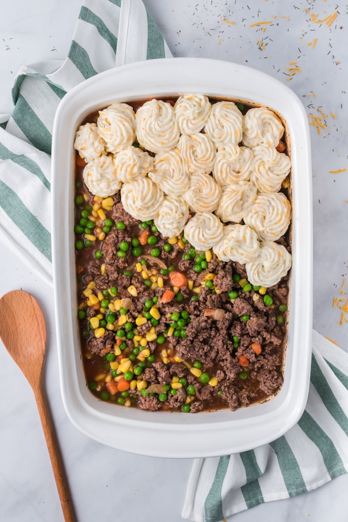 Shepherd's Pie in a casserole dish with mashed potatoes being piped on top.