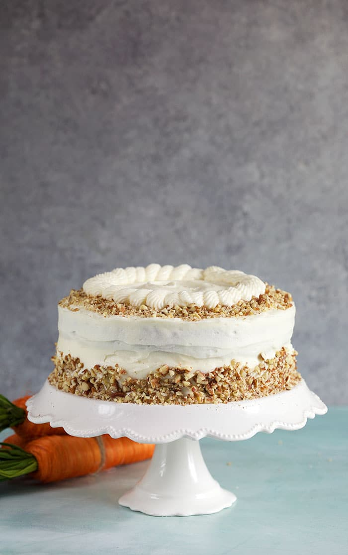 Whole carrot cake on a white cake pedestal on a gray background.