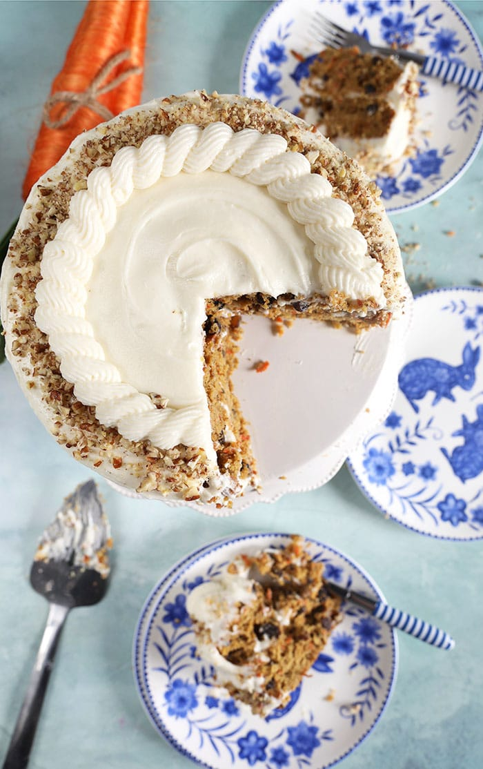 overhead shot of carrot cake on a cake plate with a slice on a blue and white plate.