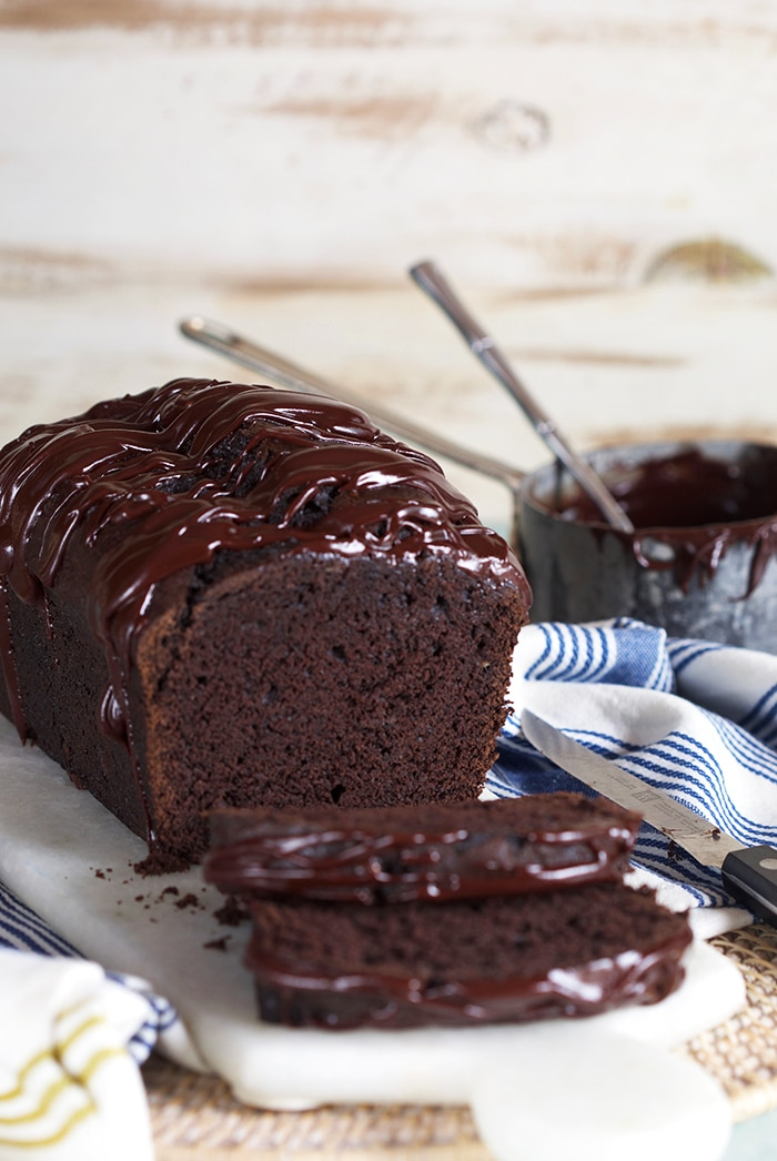 Double Chocolate Banana bread with a pot of chocolate glaze in the background.