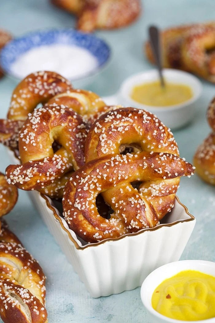 Soft pretzels in a white baking dish on a blue background.