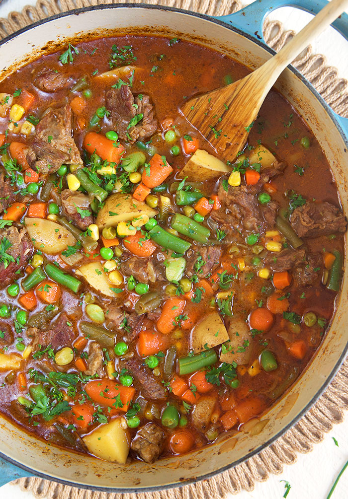overhead shot of mulligan stew in a stock pot with a wooden spoon.