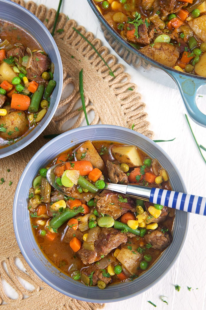 overhead shot of two bowls of mulligan stew on a white background.