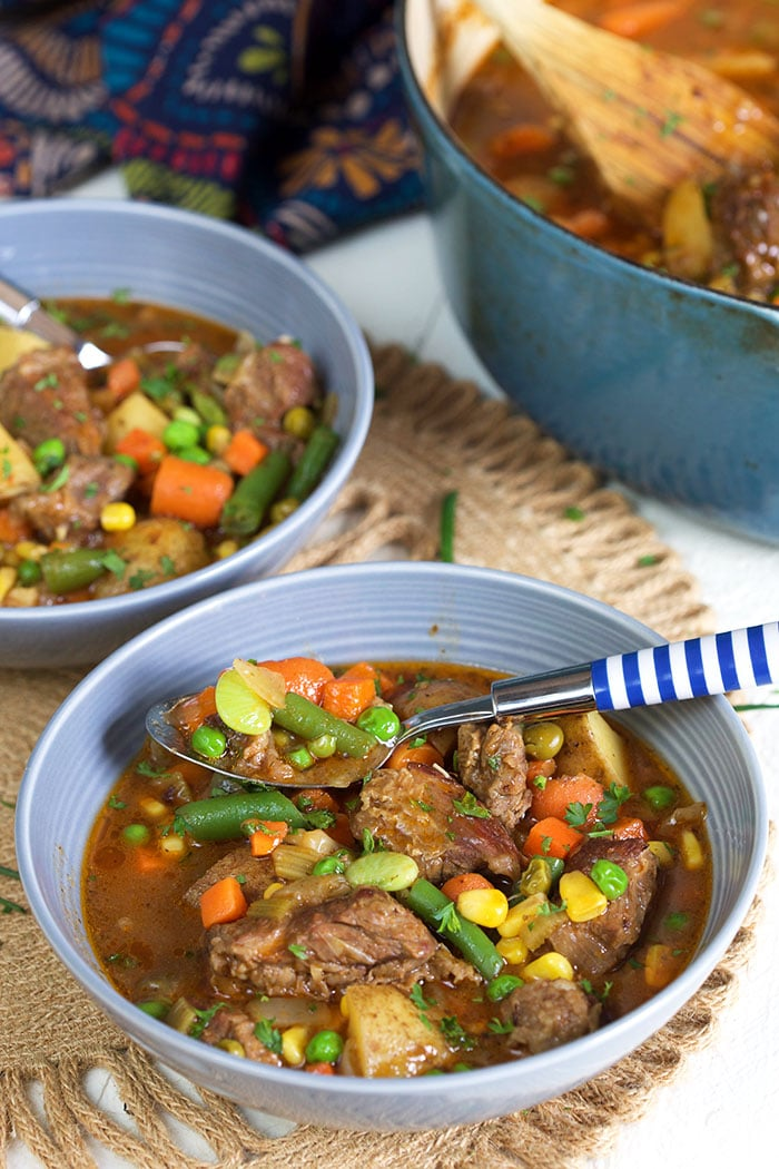 Beef Stew in a gray bowl with a blue and white striped spoon.