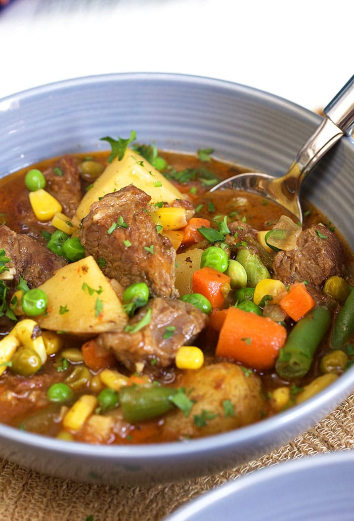 Close up of Mulligan stew in a gray bowl with a spoon.